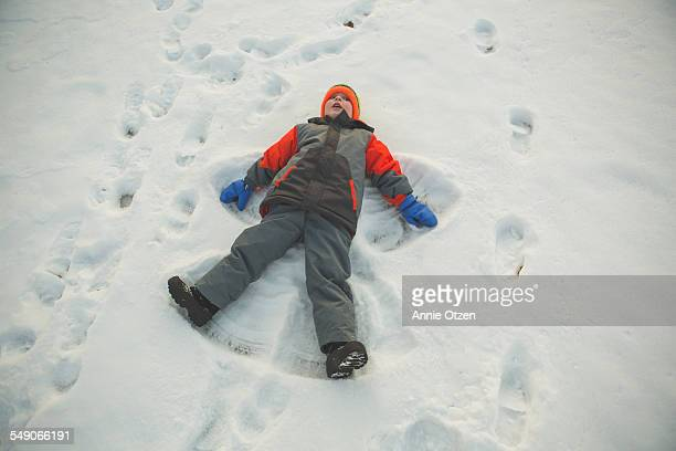 little boy making snow angel - snow boot stock photos and pictures