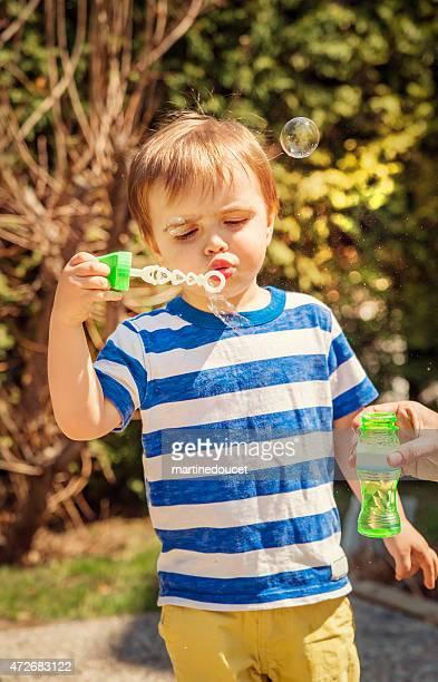 Piccolo ragazzo fare bolle di sapone per la prima volta all'aperto.