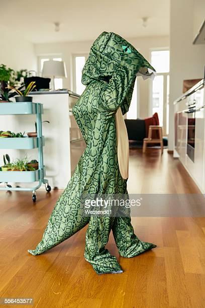 Little boy masquerade as dinosaur dancing at home