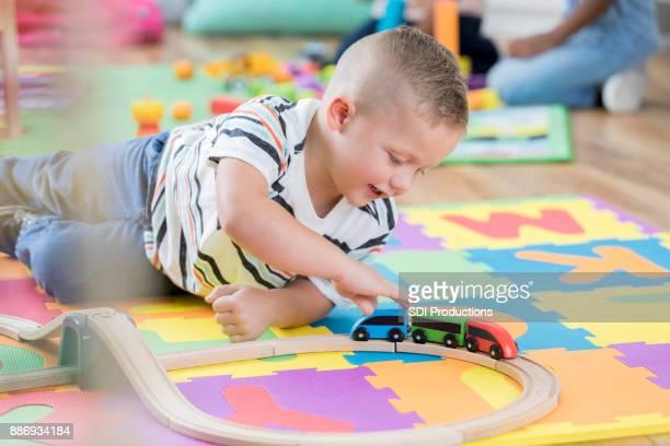niño mueve el tren de juguete a lo largo de su trayectoria - estera fotografías e imágenes de stock