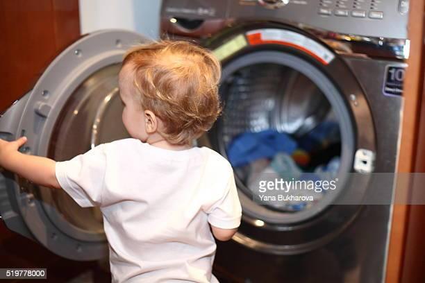 Little boy near the washing machine