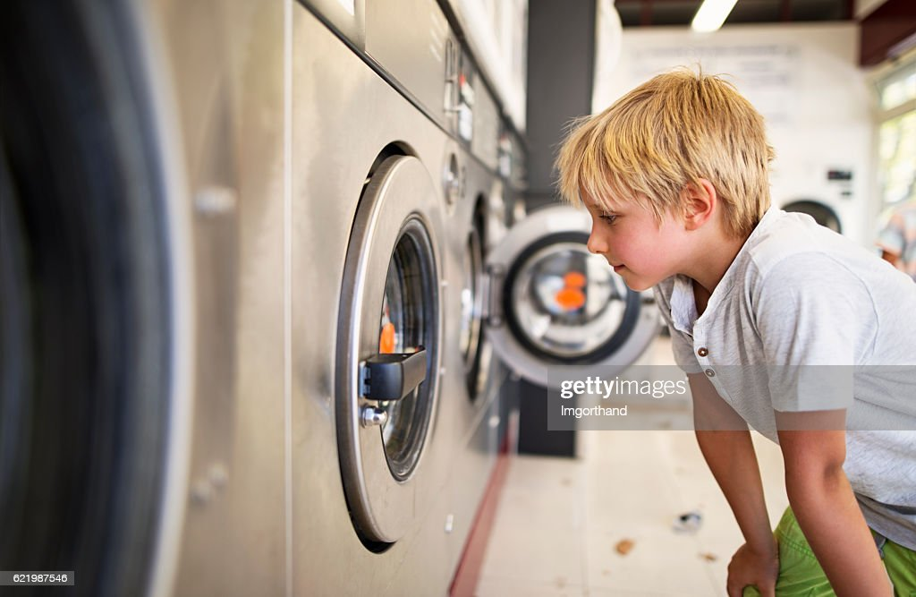 Little boy observing working laundromat in self-service laundry : ストックフォト
