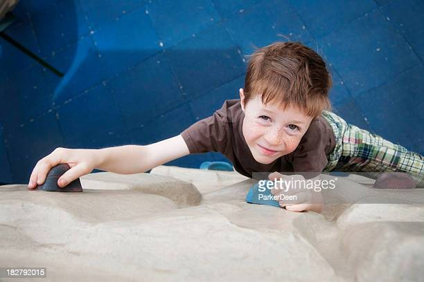 Little boy on a climbing wall at a playground