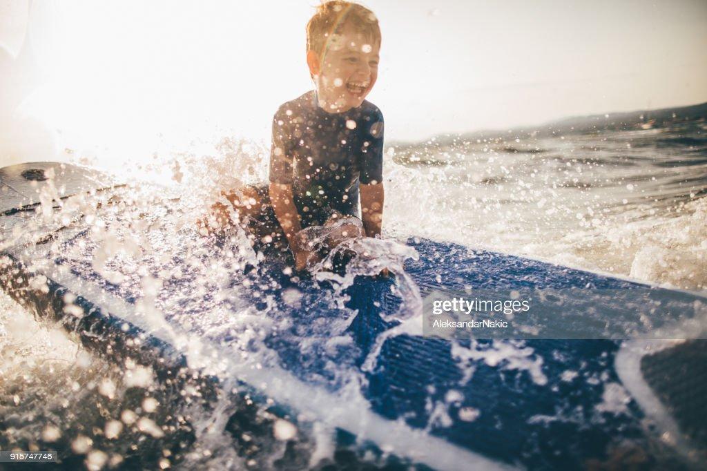Menino em uma prancha de surf : Foto de stock