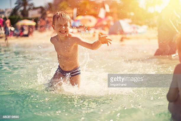 Little boy on beach having fun in sea splashing