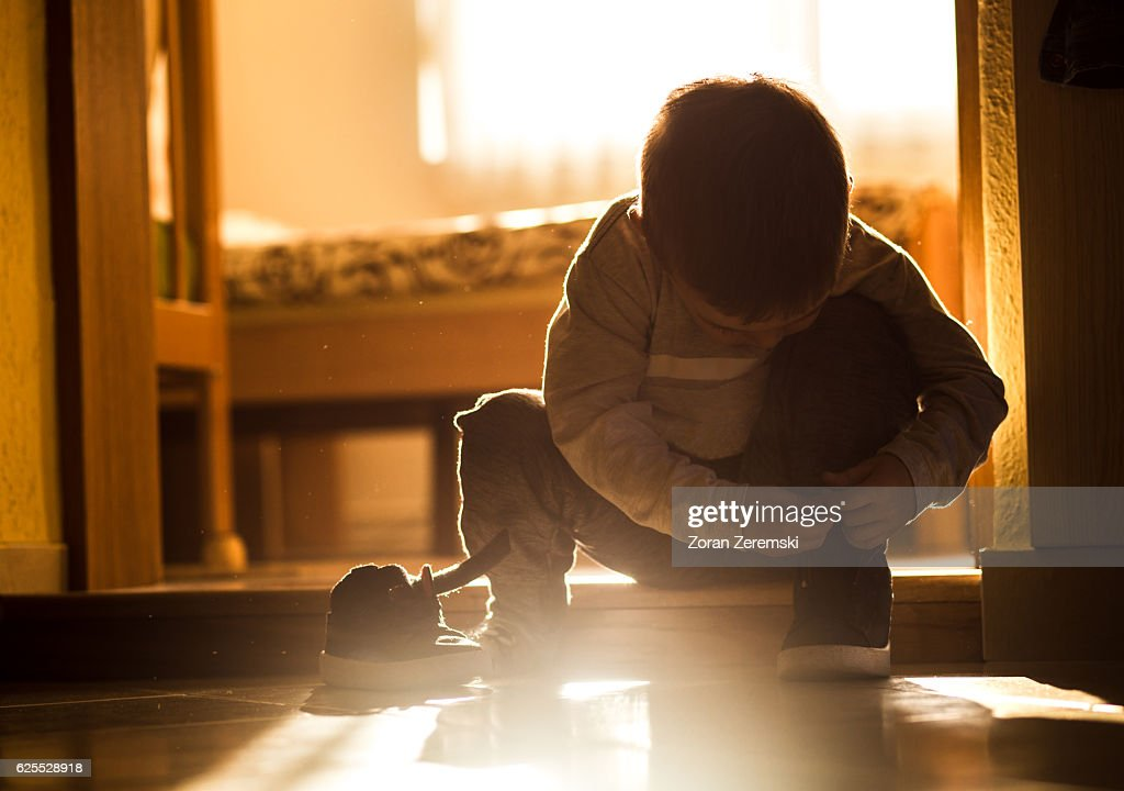 Little boy on doorstep trying to put his shoes on : Stock Photo