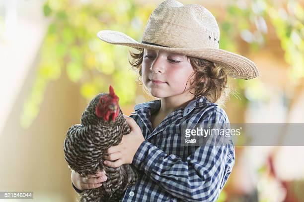 Little boy on farm holding a chicken