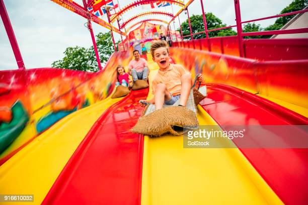 little boy on slide at a funfair - traveling carnival stock pictures, royalty-free photos & images