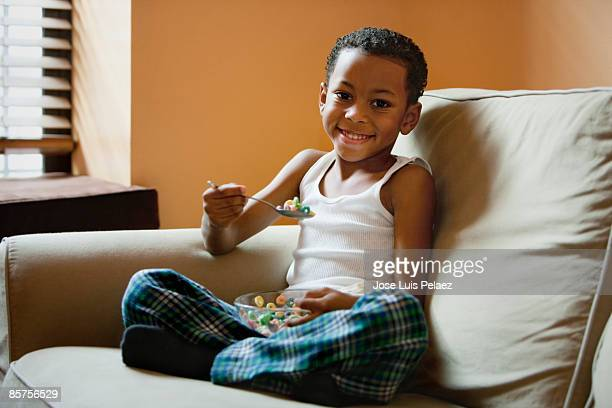 Little boy on sofa eating cereal