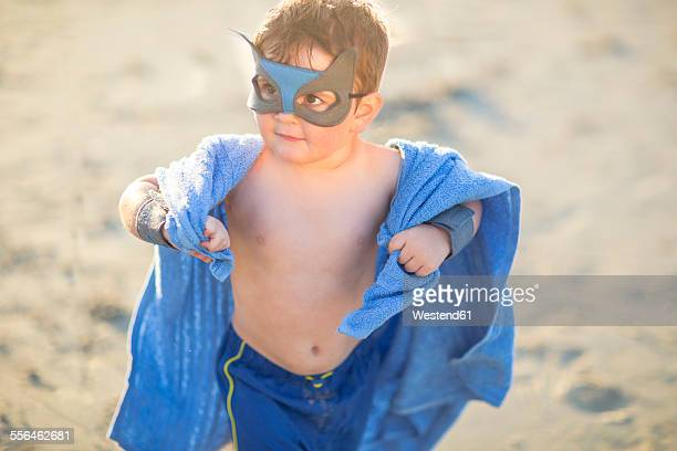 Little boy on the beach dressed up as a superhero with mask and towel