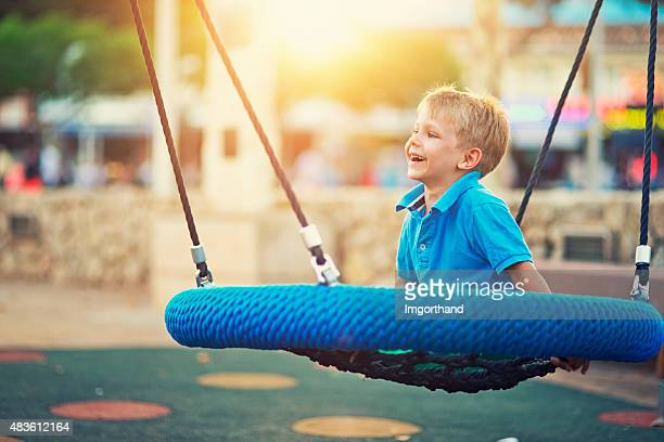 Little boy on the playground, swinging on a big swing