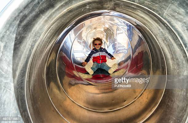 Little boy on tunnel slide