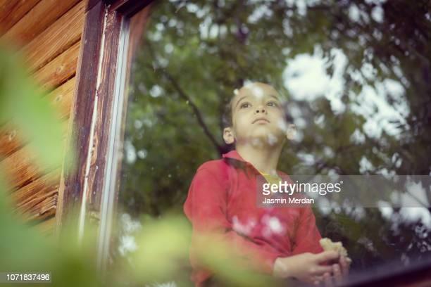 Little boy on window in cottage