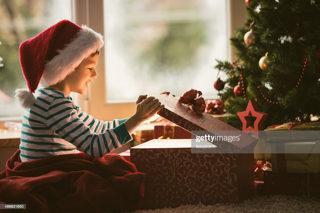 Little boy opening Christmas present : Stock Photo