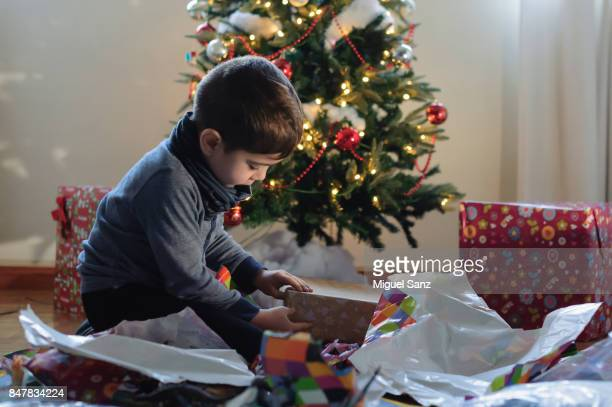 Little boy opening Christmas present with Christmas tree