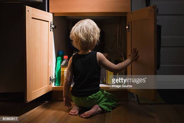 little boy opening cupboard of cleaning products - toxin stock pictures, royalty-free photos & images