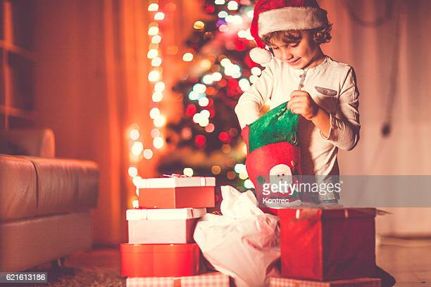 Little boy opening his Christmas gifts