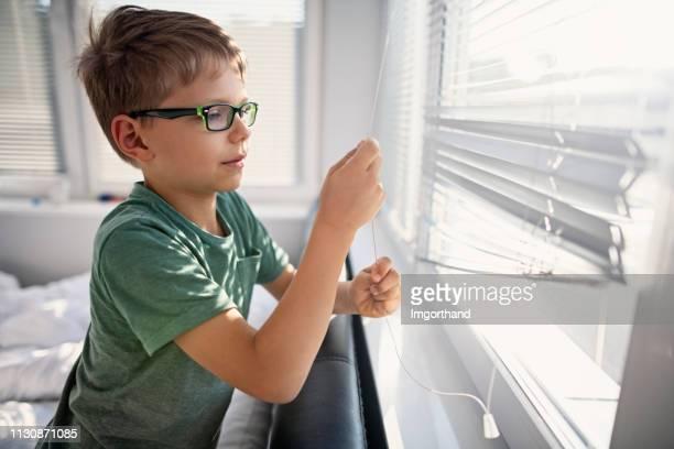 朝のブラインドを開ける小さな男の子 - 日よけ ストックフォトと画像