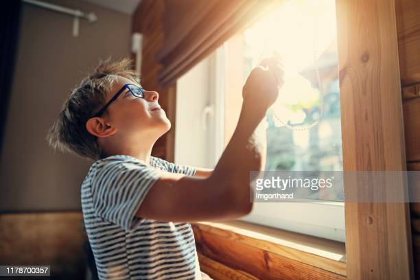 rapaz pequeno que abre as cortinas de rolo na manhã - janela - fotografias e filmes do acervo