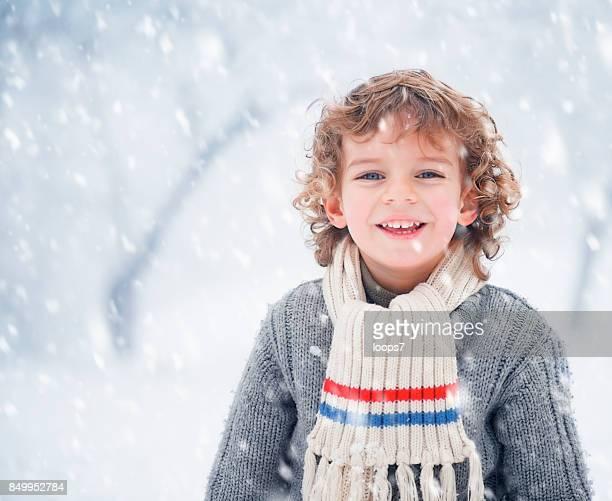 Niño al aire libre. Enormes copos de nieve nevando.