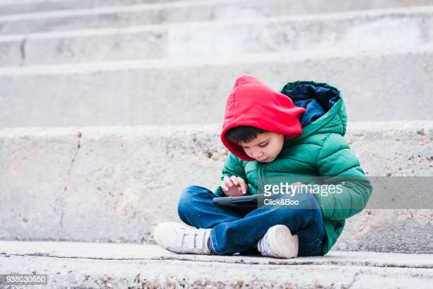 Little boy outdoors in a coat with a tablet