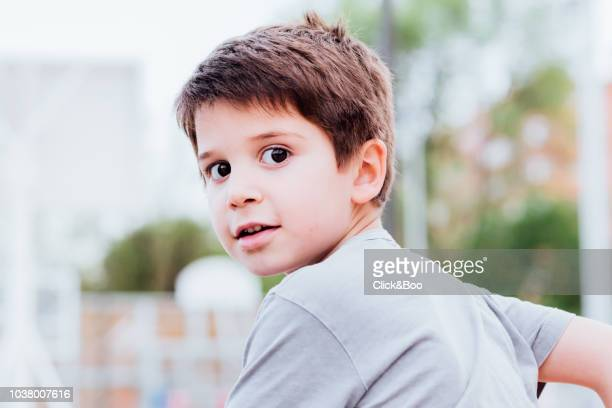 Little boy outdoors in a park looking at camera with a smile