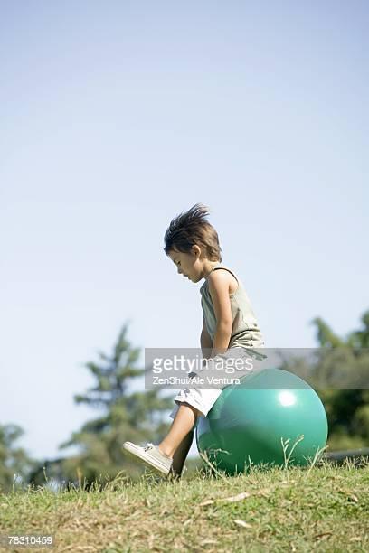 Little boy outdoors sitting on ball, full length