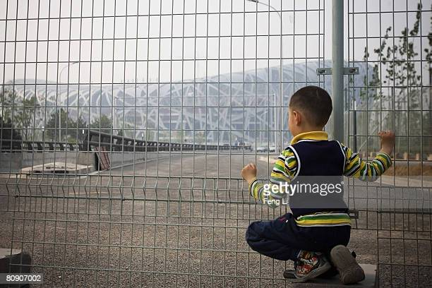 Little boy overlooks the National Stadium, or 'Bird's Nest', through the wire netting on April 29, 2008 in Beijing, China. Olympic venues 'Bird's...