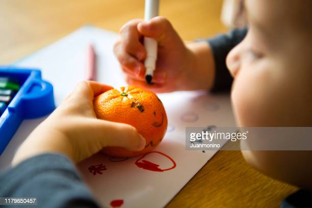幼稚園でみかんを描く小さな男の子 - ミカン ストックフォトと画像