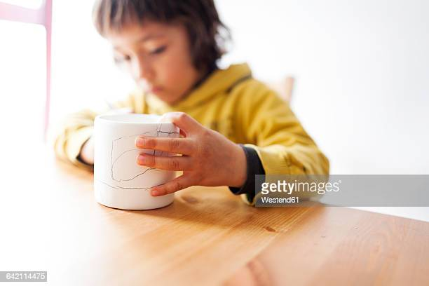Little boy painting and decorating a mug