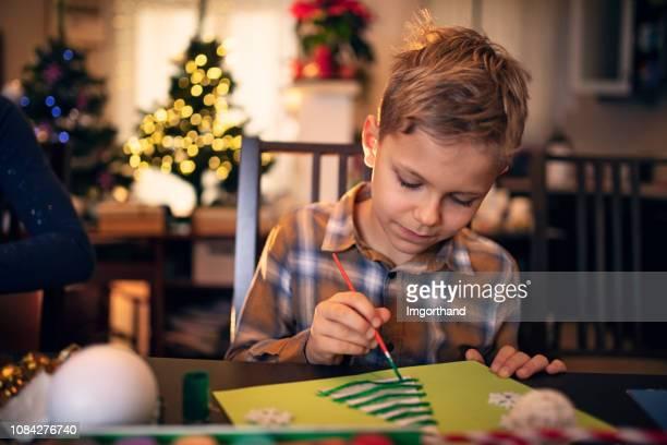 kleine junge malerei weihnachtskarte - basteln stock-fotos und bilder