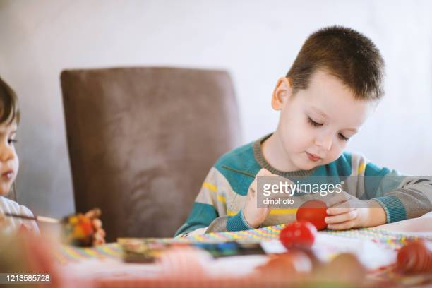 little boy painting easter eggs at the table - dirty easter stock pictures, royalty-free photos & images
