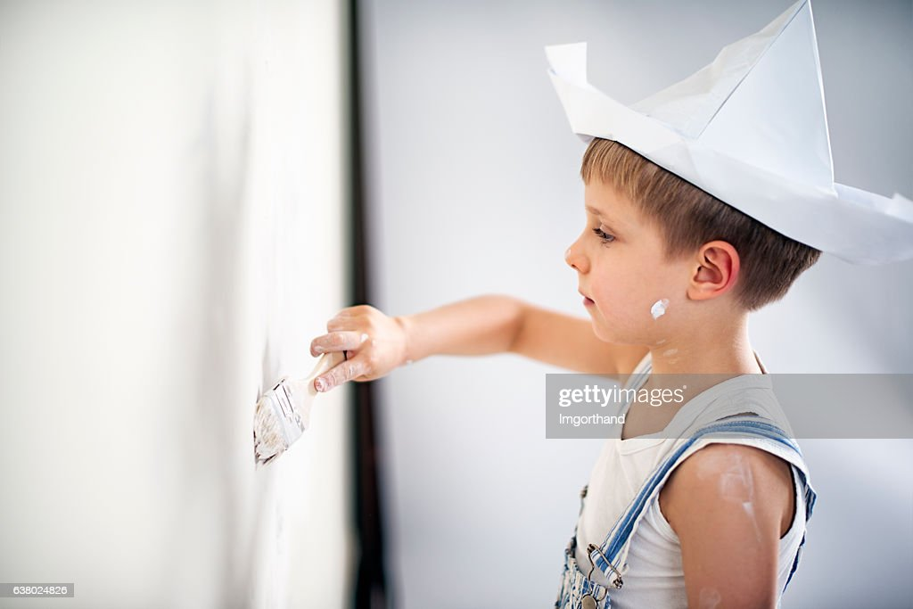 Little boy painting his room : Stock Photo