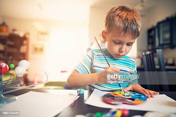 Little boy painting solar system model