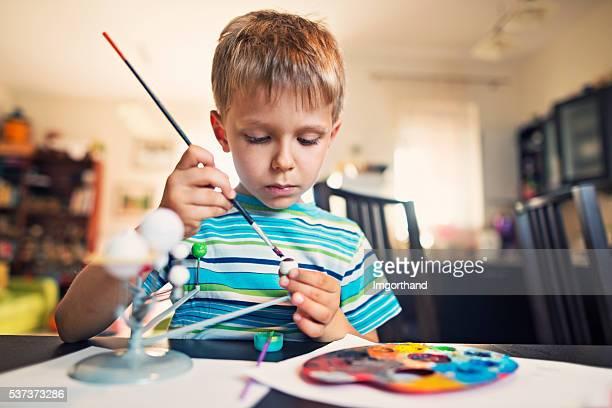 Little boy painting solar system model