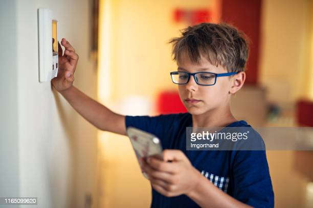 little boy pairing smartphone with smart home system - intercom stock pictures, royalty-free photos & images
