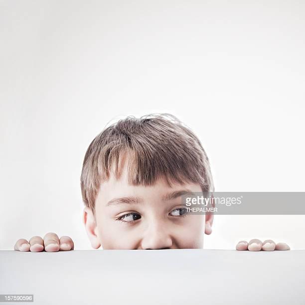 little boy peeking over a table
