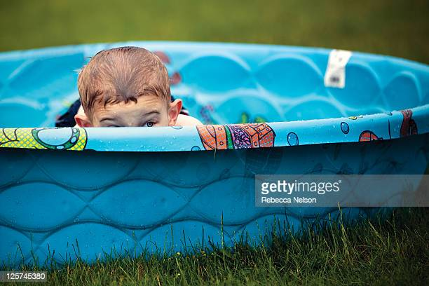 Little boy peeking over edge of wading pool