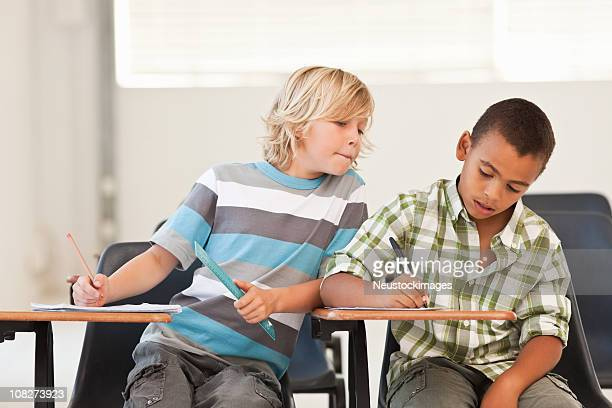 little boy peeping in classmates examination paper - dishonesty stock pictures, royalty-free photos & images