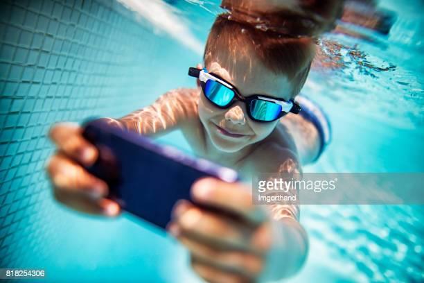 Little boy photographing underwater