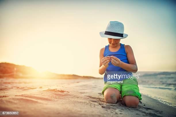 Petit garçon, ramasser des coquillages sur la plage