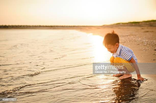 Little boy play in the water at the beach.