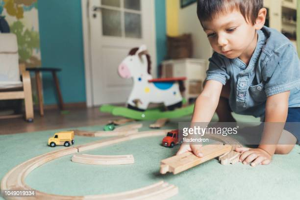 kleine jongen spelen met houten trein - alleen jongens stockfoto's en -beelden