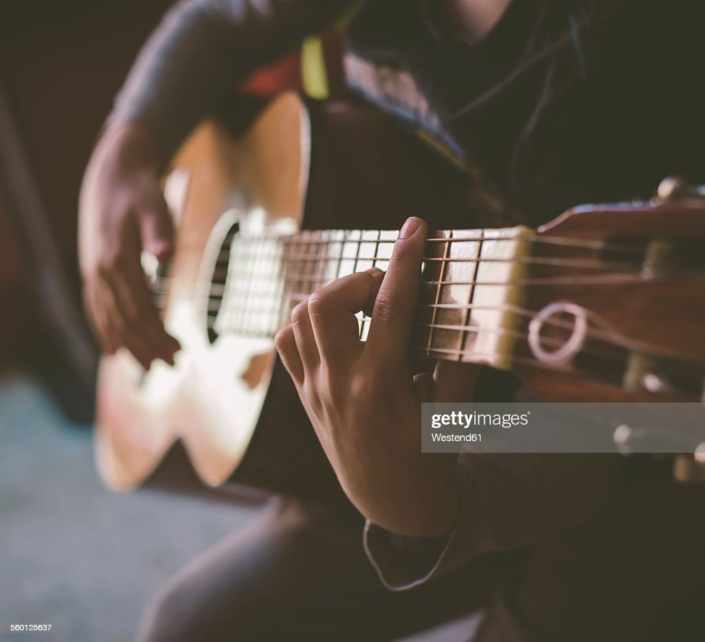 Little Boy Playing Acoustic Guitar At Home Close Up