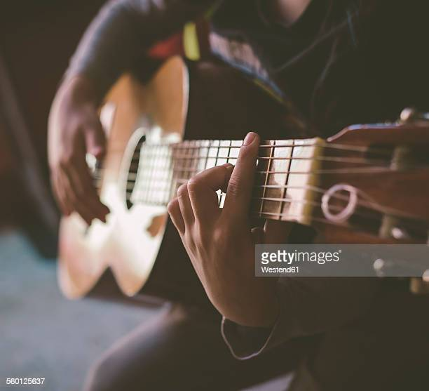 Little boy playing acoustic guitar at home, close-up