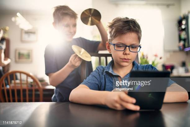 little boy playing an april fools day prank on brother - april fools day stock pictures, royalty-free photos & images