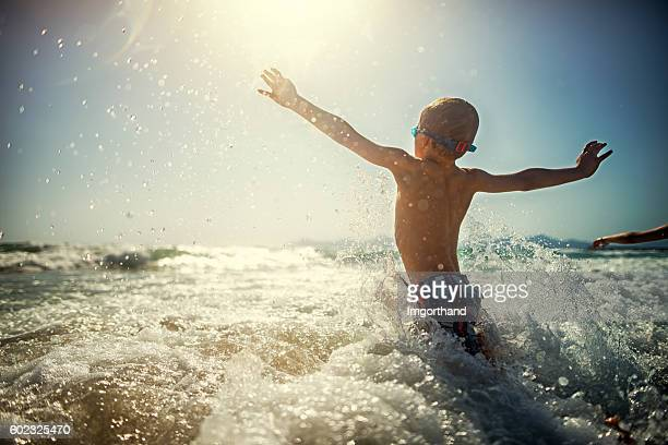 Little boy playing and splashing in sea waves