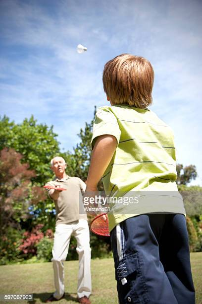 Little boy playing badminton with his grandfather