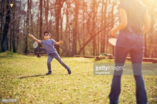 Kleiner Junge mit seiner Mutter Badminton spielen