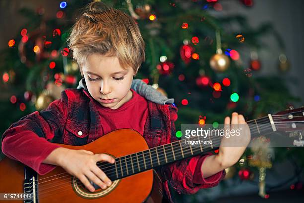 Little boy playing carols on guitar near the christmas tree